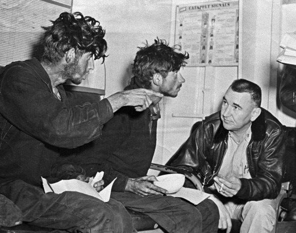 Военнослужащие Филипп Поплавский (слева) и Асхат Зиганшин (в центре) разговаривают с американским моряком (справа) на авианосце «Кирсардж», принявшем их на борт после длительного дрейфа на барже. Фото: РИА Новости
